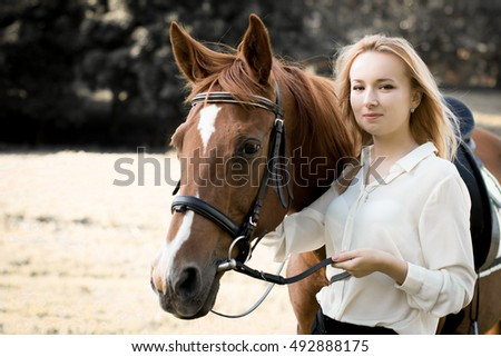 young girl with blonde hair next to a brown horse