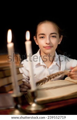 Young girl with book and candles at night library - stock photo