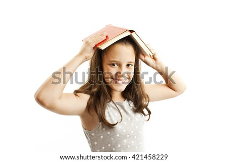 Young girl with book over her head. Isolated on white background - stock photo