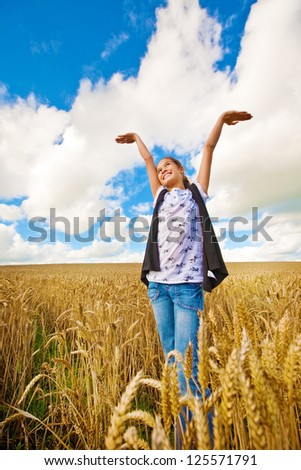 Young girl with both arms up in sky standing in wheat field - stock photo
