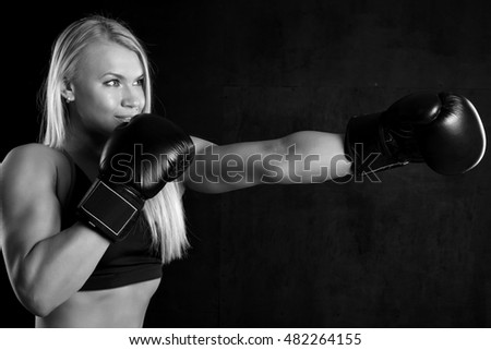 young girl with boxing gloves on a black background