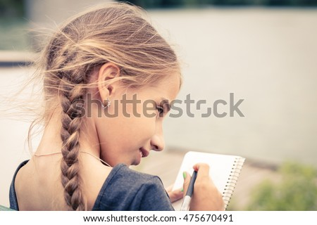 Young girl with braids drawing sketch in notebook sitting near a pond. Warm color toned image