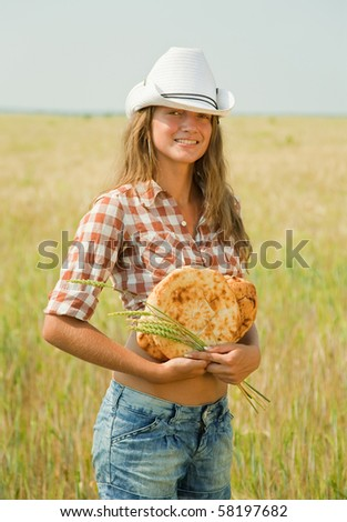 Young girl with bread at cereals field in summer - stock photo