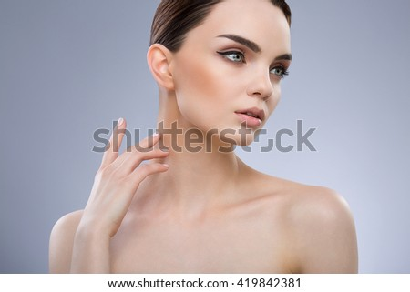 Young girl with brown hair fixed behind, big eyes, dark eyebrows and naked shoulders looking right and touching her neck, portrait, beauty photo. - stock photo