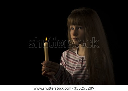 Young girl with burning candle - on the black background.