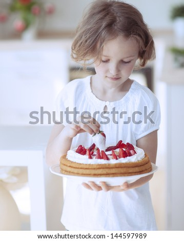 Young girl with cake and strawberries - stock photo