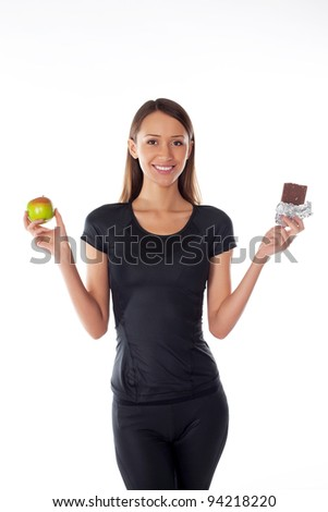 young girl with chocolate and apple in the hands on a white - stock photo
