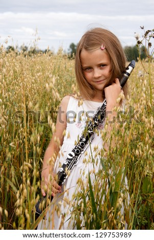 Young girl with clarinet at cornfield - stock photo