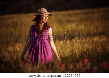 Young girl with closed eyes on field - stock photo