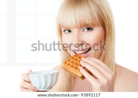 Young girl with coffee bitting a piece of belgian waffle