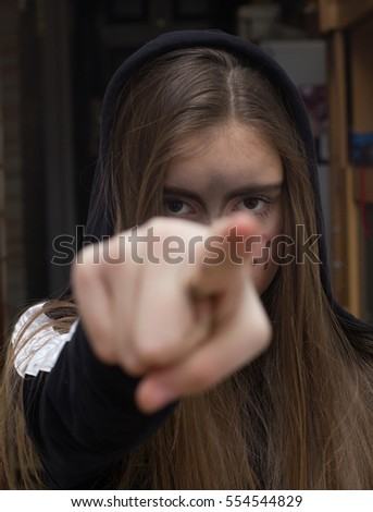 Young girl with colored face pointing by fingers