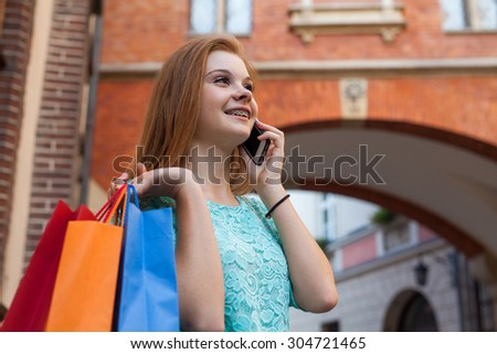 Young girl with colorful shopping bags calling her friend