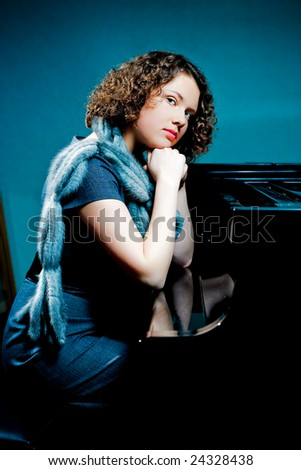 young girl with curly hair sitting near black piano with hands crossed isolated - stock photo