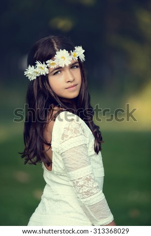 Young girl with daisy chain headband - stock photo
