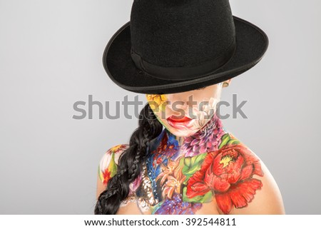 Young girl with dark long hair wearing black hat, body art paintings on neck, shoulders and face, painting flowers, make up model, portrait, gray background. - stock photo