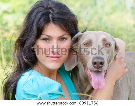 Young girl with  dog in meadow - stock photo