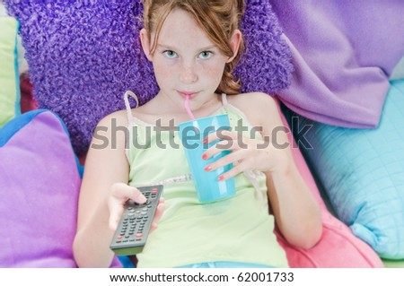 Young girl with drink watching TV in bed - stock photo