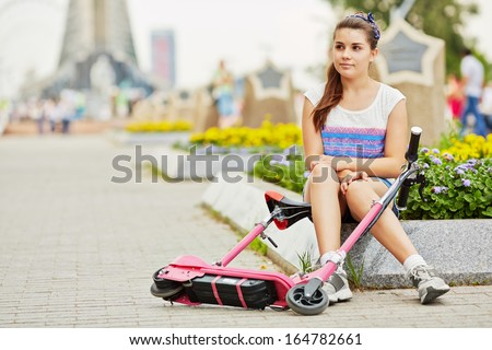 Young girl with electrical scooter sits on curb of flower bed at square - stock photo