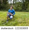 Young girl with eyes closed giving thanks after landing a large trout with woods in background - stock photo