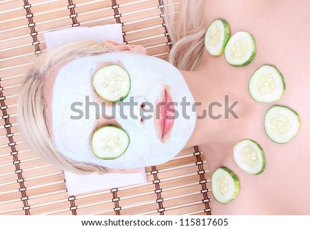 young girl with facial mask of cucumber on bamboo mat ,  spa - stock photo