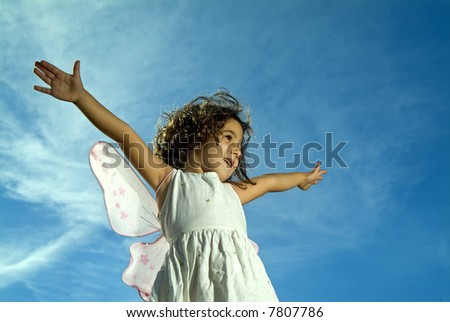 young girl with fairy wings flying against blue sky with cirrus clouds - stock photo