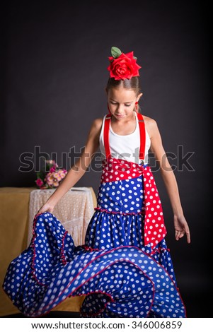Young girl with flamenco outfit dancing on black background - stock photo