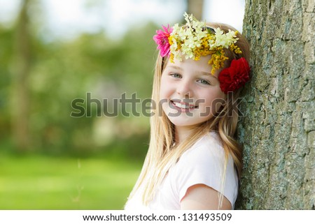 young girl with floral wreath leaning on a tree - stock photo