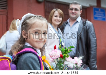 Young girl with flower and school bag looking at camera with her parents - stock photo