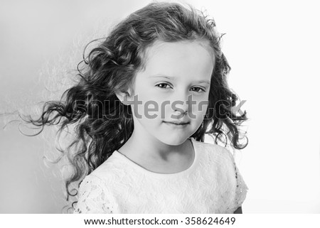 Young girl with flying hair. Black and white portrait. - stock photo