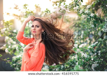Young girl with flying hair in a lush garden walks spring day - stock photo