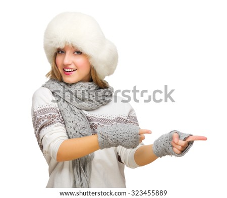 Young girl with fur hat showing pointing background isolated - stock photo