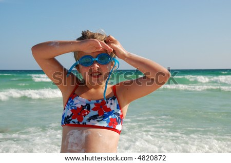 Young girl with goggles and messy suntan lotion on her body