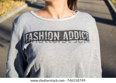"Young girl with gray loose sweatshirt that has ""Fashion Addict"" written on it. Concept of fashion, shopping, consumers. Pitesti,Romania,Europe October 30 2017"
