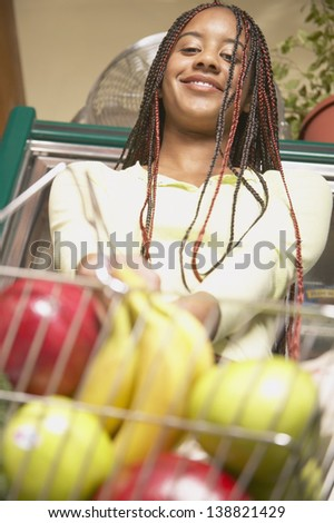 Young girl with groceries in basket - stock photo
