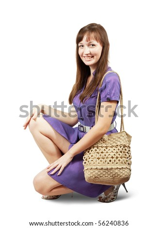 young girl with handbag sitting on white background - stock photo