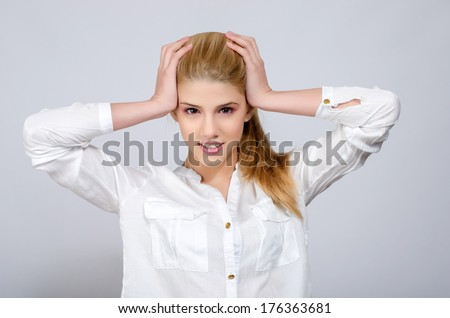 Young girl with hands on her head being desperate. Beautiful young blonde girl in white shirt.  - stock photo