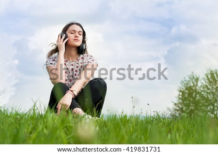 Young girl with headphones on her head sitting on grass and listening music with copyspace - stock photo