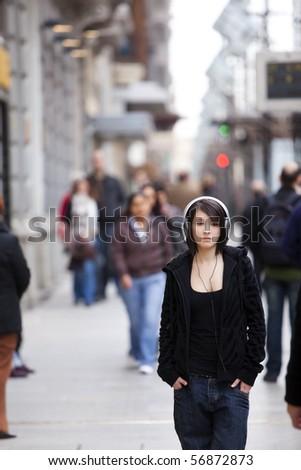 Young girl with headphones standing on sidewalk - stock photo