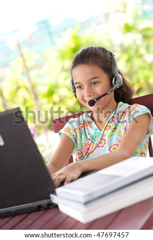 Young girl with headset and using the laptop computer, on the outdoor terrace - stock photo
