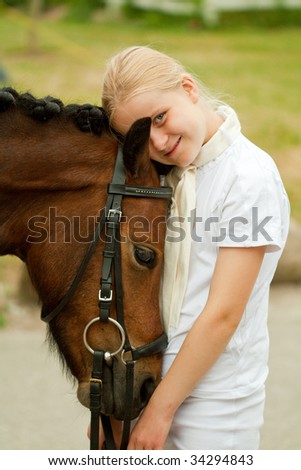 Young girl with her pony - stock photo