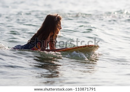 young girl with her surfboard in the sea
