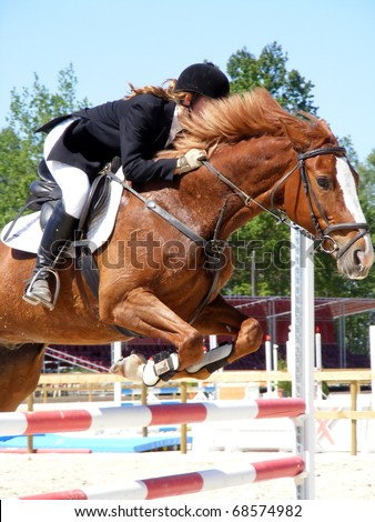 Young girl with hidden face jumping with brown horse - stock photo
