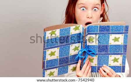 Young Girl With Huge Eyes in Exclamation Over What She's Reading - stock photo