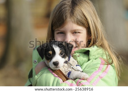 Young girl with Jack Russell Terrier puppy cuddling outdoors. Focus on the puppy.