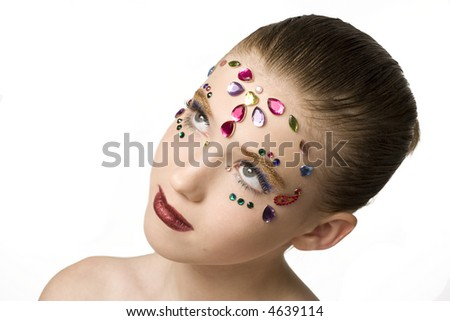 Young girl with jewels on her face.