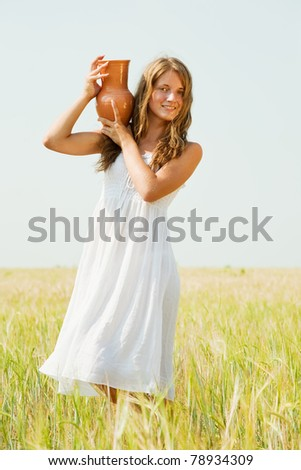 Young girl  with jug at cereals field in summer - stock photo