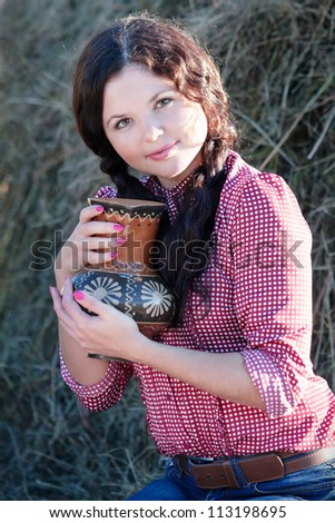 Young girl with jug at cereals field in summer. Rural scene.