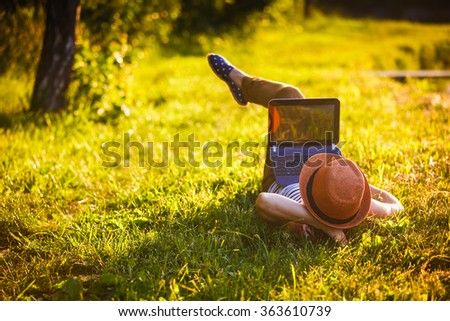 young girl with laptop working outdoor  - stock photo