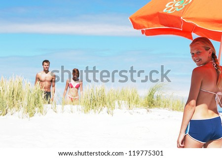 Young girl with large orange beach umbrella smiling back over her shoulder at the camera as her parents approach across the sand dunes - stock photo