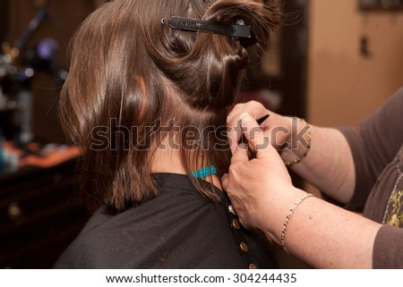 Young girl with long brown hair getting a haircut at a hair salon - stock photo